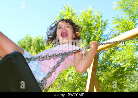 Girl swinging swing in outdoor park nature low angle view - Stock Photo
