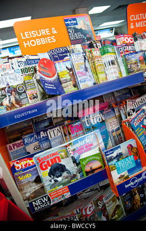 Shelves full of assorted UK weekly and monthly magazines and periodicals in a branch of high street newsagents WH - Stock Photo