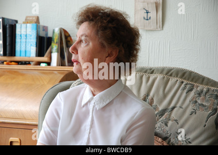 OAP lady sitting in a chair at home staring out - Stock Photo