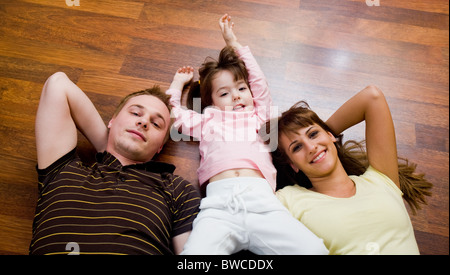 View from above of cheerful family members lying on the floor and looking at camera - Stock Photo