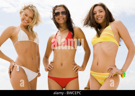 Portrait of three slim girls in bikini smiling at camera on the beach - Stock Photo
