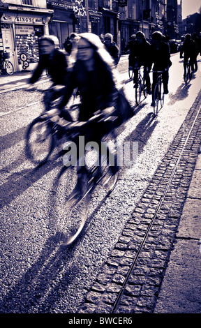 Students cycling to lectures in Cambridge in strong early winter sun - Stock Photo