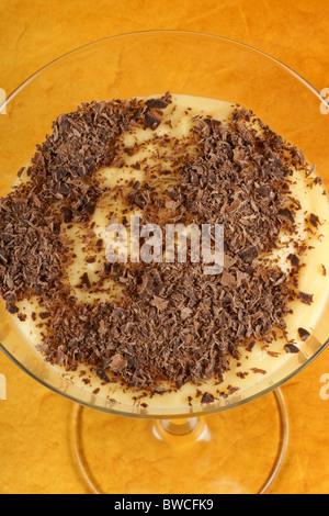 Vanilla custard cream with chocolate dessert served in a glass over an orange background. - Stock Photo