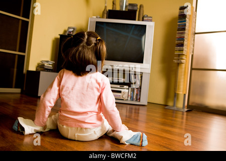 Rear view of little girl sitting on the floor and watching TV in living-room