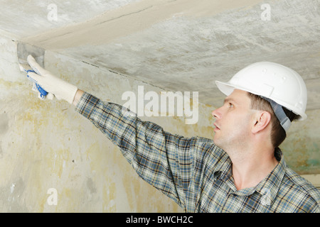 Contractor plastering the ceiling - Stock Photo