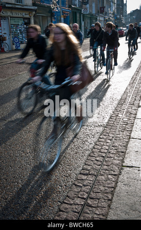Students cycling to lectures in Cambridge in strong early winter sun