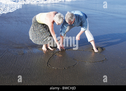 USA, California, Fairfax, Happy mature couple drawing heart on beach - Stock Photo