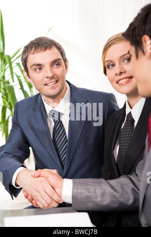 Photo of successful business partners handshaking after striking deal with their colleague smiling - Stock Photo
