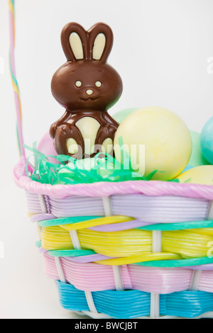 Studio shot of Easter eggs and chocolate bunny in basket - Stock Photo