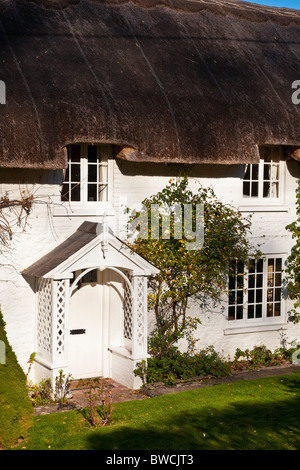 A typical pretty English stone thatched cottage in the Wiltshire village of Broad Chalke, England, UK - Stock Photo