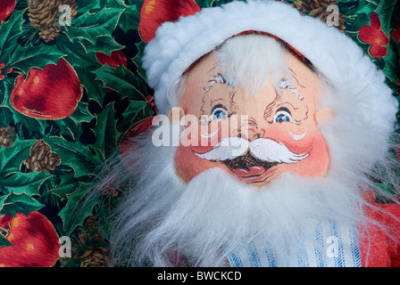 Santa Claus closeup. Painted fabric face with hat & beard on apple & holly background. - Stock Photo