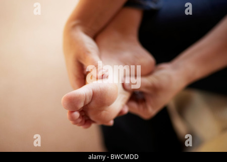 Woman massaging foot - Stock Photo