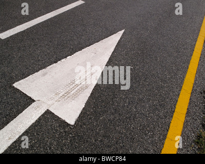 White arrow on road indicating direction for traffic to follow. Tyre mark imbedded in paint on arrow. - Stock Photo