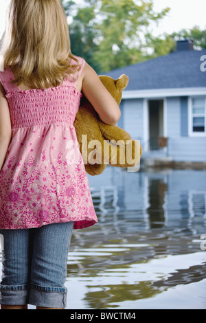 USA, Illinois, Chillicothe, Girl (6-7) standing in water and carrying teddy bear, rear view - Stock Photo