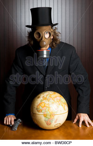 Businessman wearing a gasmask and holding a gun standing over an earth globe on a table - Stock Photo