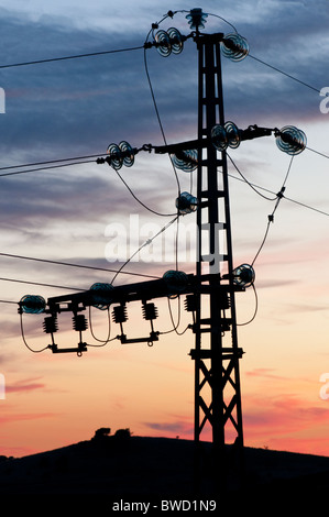 Small electricity pylon with power lines connecting in curved wires through glass insulators, silhouetted against - Stock Photo