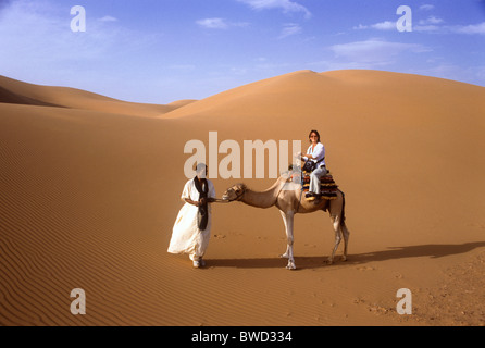 Woman Sitting on Camel with Berber Guide, Sahara Desert, Merzouga, Morocco, North Africa - Stock Photo