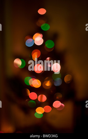 Out of focus Christmas tree, decorated with multi colored lights. - Stock Photo