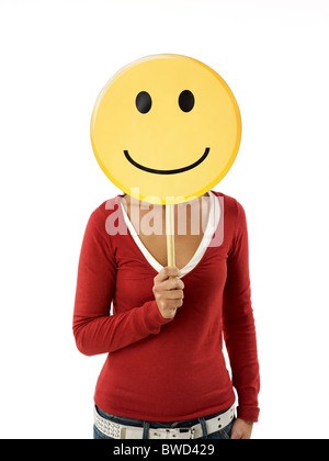 young adult woman holding smiley emoticon on white background. Vertical shape, front view, waist up - Stock Photo