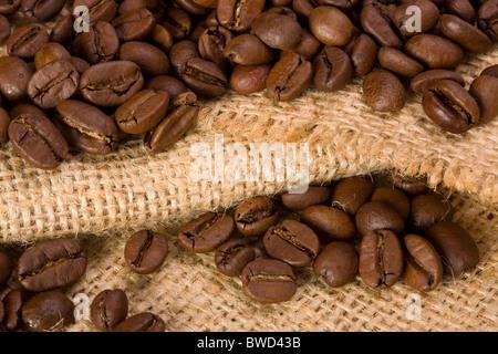 Coffee beans on burlap texture - Stock Photo