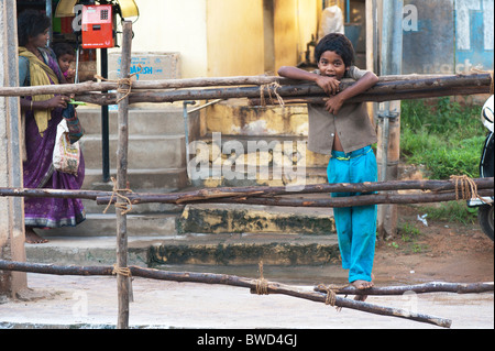 Happy young Indian street boy smiling standing on a wooden fence in the town of Puttaparhi, Andhra Pradesh, India - Stock Photo