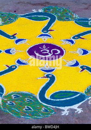 Colourful Sacred OM hindu Rangoli festival design in a street in Puttaparthi, Andhra Pradesh, India - Stock Photo