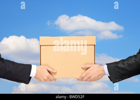 A businessman delivering a package to a man isolated on blue sky - Stock Photo