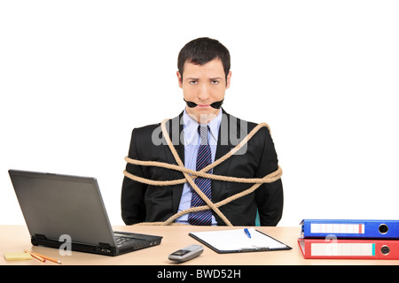 A businessman tied up with rope and gagged with band in the office - Stock Photo
