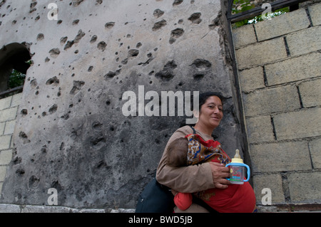 A gypsy woman carrying her baby walk past a house showing shrapnel damage from the 1992-95 war in the town of Mostar - Stock Photo