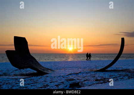 Silhouette of Passacaglia sculpture and people walking on snow covered beach during sunset. Brighton, UK JPH0272