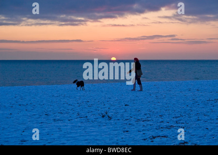 Owner and dog walking along a snow covered beach at sunset, Brighton, UK. JPH0275 - Stock Photo