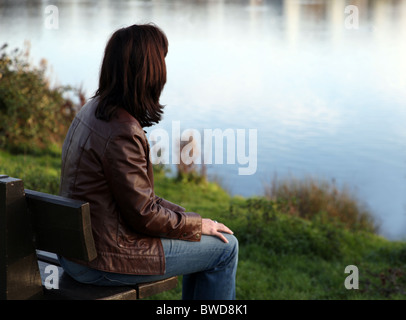Back view of a woman deep in thought  looking towards a lake, sitting on a park bench. - Stock Photo