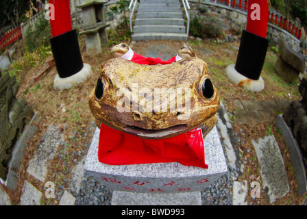 Small sub shrine at Fushimi Inari shrine with a lucky toad and red torii in the background, Kyoto, Japan - Stock Photo