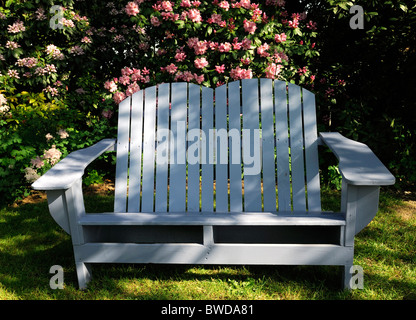 rustic white wooden wood garden seat furniture setaing pink rhododendron hedge backdrop - Stock Photo