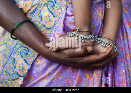Indian babies feet on mothers hands against colourful clothing.  Andhra Pradesh, India - Stock Photo