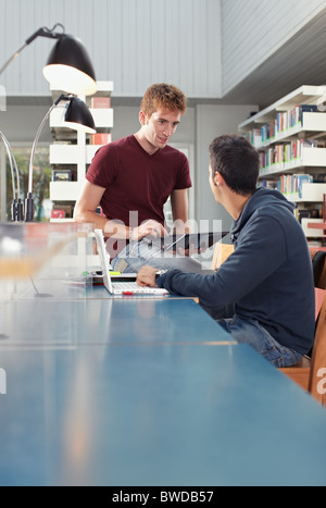 caucasian students with laptop computer talking in library. Vertical shape, copy space, focus on background - Stock Photo