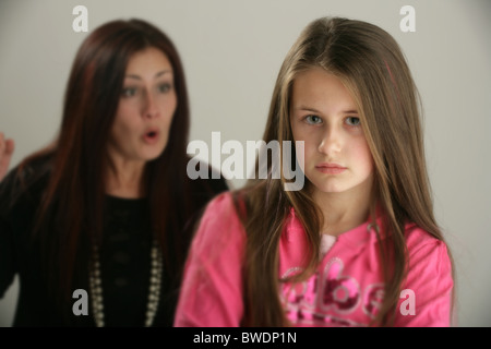 Mother telling off her ten year old daughter. - Stock Photo