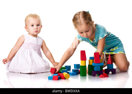 Little girl building a castle with cubes isolated on white ...