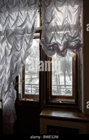 'Russian interior' view through ruched curtains and wrought iron railings on to snowy park - Stock Photo