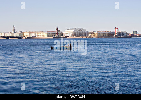 Men fishing in a boat on the'Neva River' opposite the 'Old Stock Exchange Building' 'Naval Museum' and 'Rostral - Stock Photo