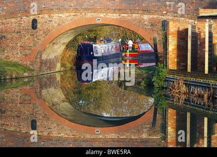 A bridge and boats reflected in the Grand Union Canal at Blisworth Arm, Northamptonshire, UK - Stock Photo