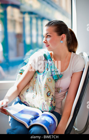 Young woman riding in tram train - Stock Photo