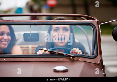 Young women driving oldtimer - Stock Photo