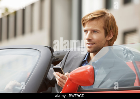 Business man on phone in an electric car - Stock Photo