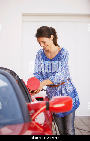 Woman plugging in her electric car - Stock Photo