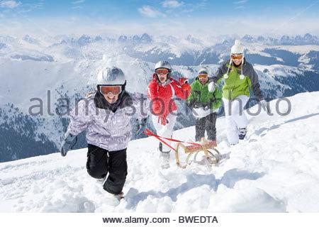 Smiling family pulling sled in snow on ski slope - Stock Photo