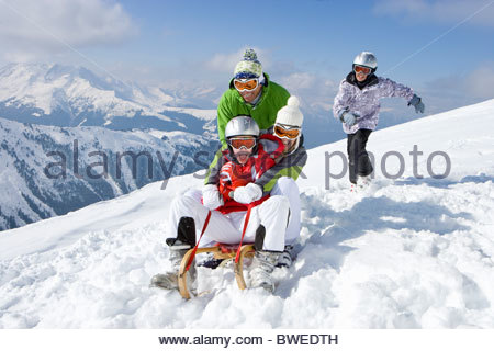 Smiling family riding sled in snow on ski slope - Stock Photo