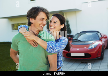 Couple in front of house + electric car - Stock Photo
