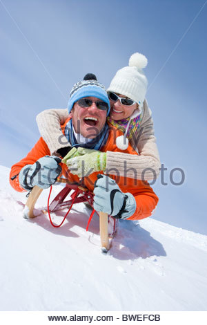 Smiling couple riding through snow on sled together - Stock Photo