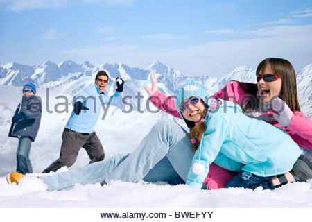 Laughing family having snowball fight together on mountain top - Stock Photo